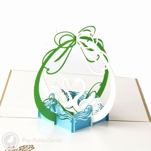 This beautiful greetings card opens to reveal a stunning 3D pop-up design showing two swans on the water below arching ribbons. The cover also shows two swans facing each other on water.