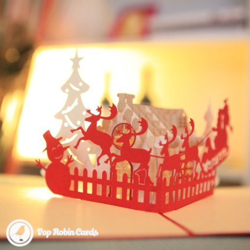 This beautiful Christmas card opens to reveal a 3D pop-up  design showing a snowman, reindeer, Santa's sleigh and a Christmas tree. The cover has a stenciled design showing snowflakes falling around a house and pine trees. It's a perfect cosy Christmas card for a festive feel.