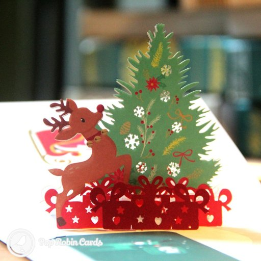 This bright and colourful Christmas card has a printed interior and a 3D pop-up scene showing Rudolf the red-nosed reindeer alongside a decorated Christmas tree. A separate inner card can be slotted in after you write your message on it.