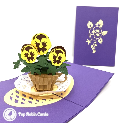 This bright and colourful greetings card is suitable for many occasions with its 3D pop up design showing a basket of yellow pansy flowers on a purple background. The cover has a stylish stencil design showing a pansy flower in yellow.