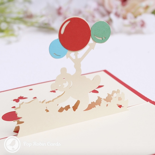 This cute greetings card opens to reveal a 3D pop-up design showing a teddy bear floating beneath brightly coloured balloons. The cover has a stencil design also showing the bear and balloons.