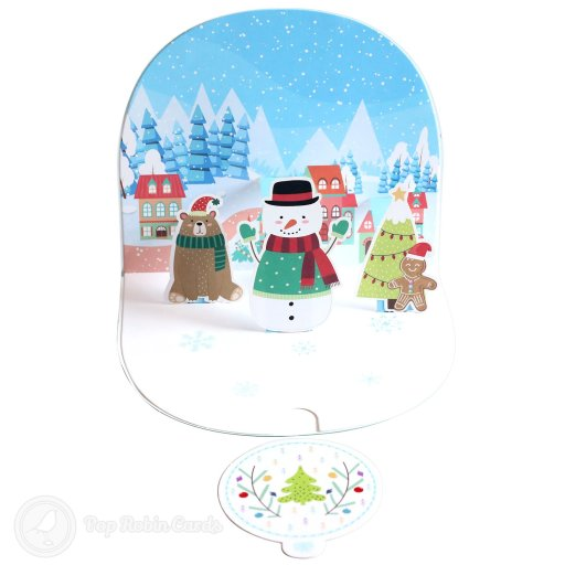 """This Christmas card opens to reveal a jolly 3D pop-up scene showing a snowman, a bear and a gingerbread man in the snow with cosy houses in the background. The cover has a special curved design and a """"Merry Xmas"""" message."""