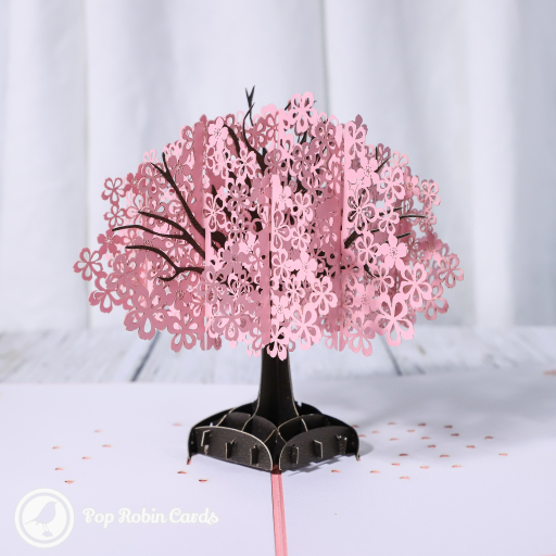 This beautiful greetings card is suitable for all sorts of occasions with its 3D pop up design showing a gorgeous pink cherry blossom tree. The cover has a stencil design showing the tree surrounded by a pretty picket fence.