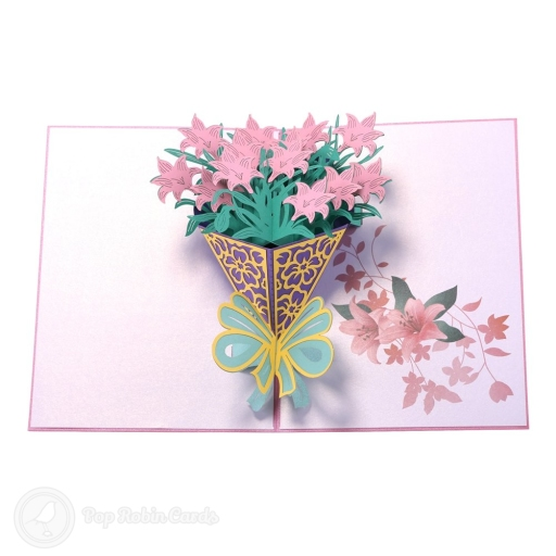 This beautiful card opens to reveal a 3D pop-up design showing a bouquet of unusual pink daffodils wrapped with ribbons. The cover is floral pink and has a stencil design.