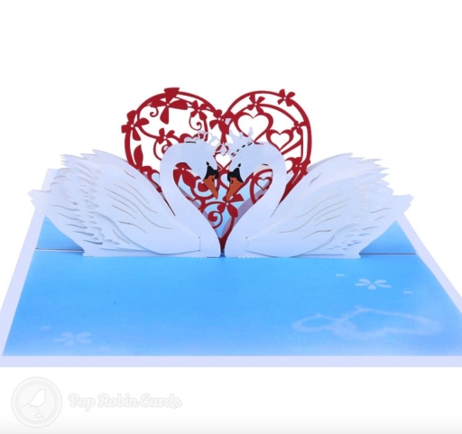 This beautiful romantic card opens to reveal a 3D pop-up design showing two swans gazing at each other on water, with a red heart trellis design behind them.