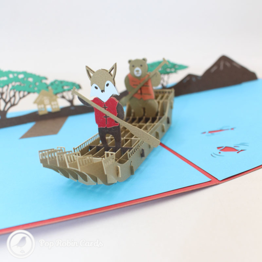 This charming 3D pop up card shows a fox and a bear rowing down a river together with trees and a house in the background. The cover has a stencil design showing a bear paddling in a boat.