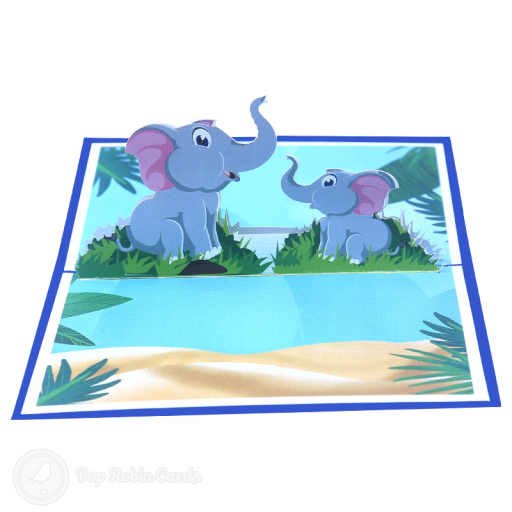 This cute greetings card opens to reveal a 3D pop-up design showing two cartoon elepehants, one big elephant and one baby elephant, sitting beside a watering hole. The cover has a stylised elephant design.