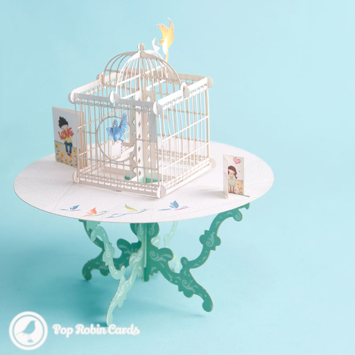 This unusual greetings card folds flat but opens up into a 3D pop up design showing birds delivering letters around a birdcage, and miniature cards either side.