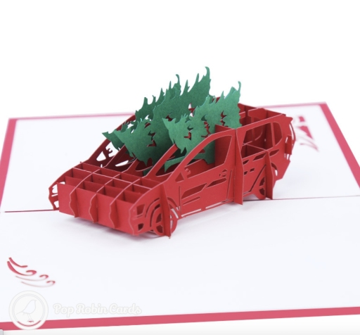 """This quirky Christmas card has a 3D pop up design showing a car laden with several large, green Christmas trees. The cover has a stencil design with a """"Merry Christmas"""" message."""