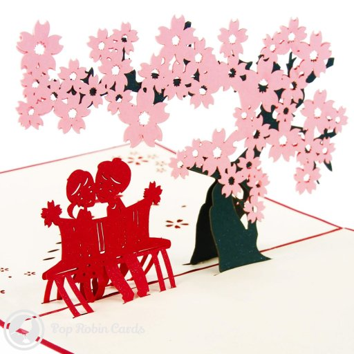 This lovely greetings card opens to reveal a beautiful 3D pop-up scene with pink cherry blossoms above a young couple sitting together on a park bench. The cover has a stenciled design depicting the same scene. It's a cute romantic card to give to someone special.
