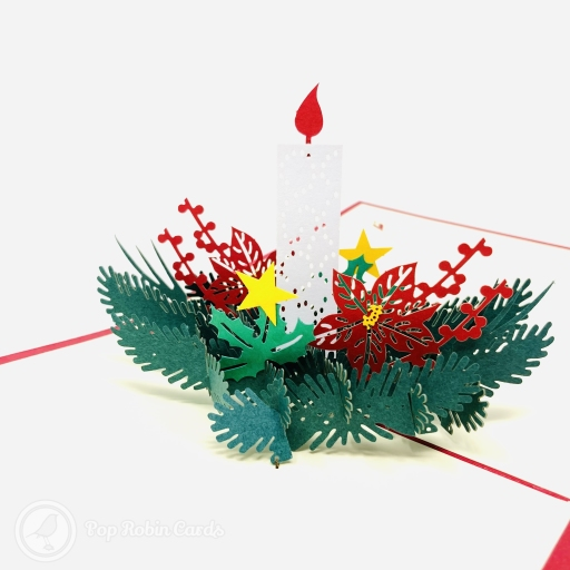 This traditional Christmas card opens to reveal a 3D pop up design showing a Christmas candle surrounded by holly.