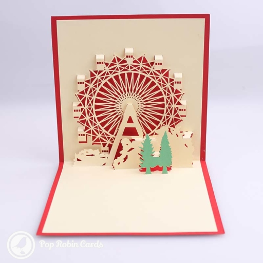 This charming Christmas card has a 3D pop up design showing a ferris wheel behind two green Christmas trees. The cover has a stencil design also showing a ferris wheel.