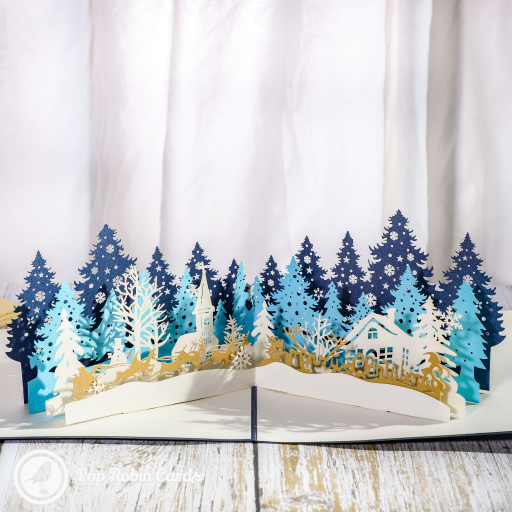 This atmospheric Christmas card captures a special Christmas scene with its 3D pop up design showing a traditional village in a snowy winter forest, with Santa riding through on his sleigh pulled by reindeer.