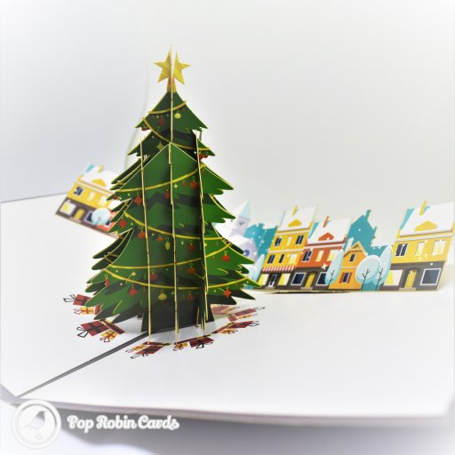 "This colourful Christmas card opens to reveal a 3D pop-up scene showing a tall decorated Christmas tree surrounded by presents and cosy winter houses. The cover has a stencil Christmas tree design with the words ""Merry Christmas""."
