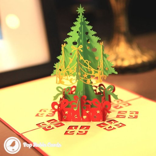 This card has a combined pop-out and stencil design, with a 3D Christmas tree in green, red and yellow standing in the middle, surrounded by stencilled presents below.