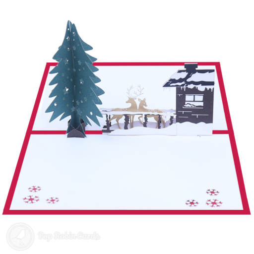 This beautiful Christmas card opens to reveal a 3D pop up design showing a tall, snowy pine tree, two reindeer and a cosy lodge in the snow. The cover has a stencil design showing the reindeer in a forest under a full moon.