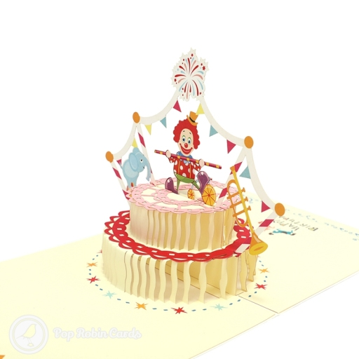 "This lively card has a 3D pop up design showing a clown dancing on top of a birthday cake, with a ""Happy Birthday"" message on each side."