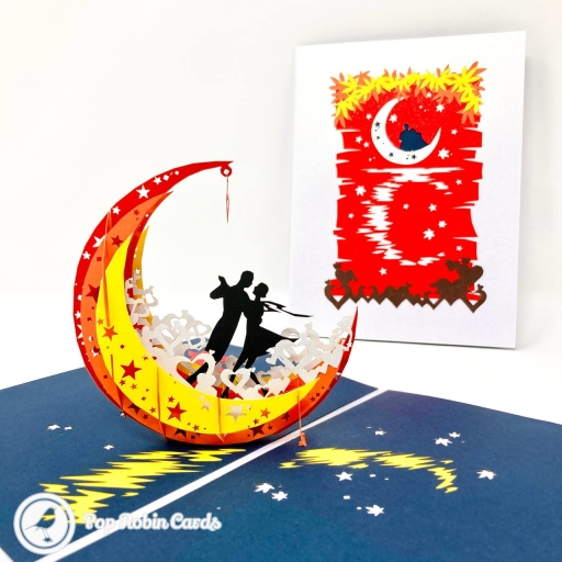 This amazing romantic card opens to reveal a 3D pop up design showing the silhouette of a couple dancing within a vivid yellow, orange and red crescent moon. The cover has a beautiful design showing the scene reflected over rippling water.