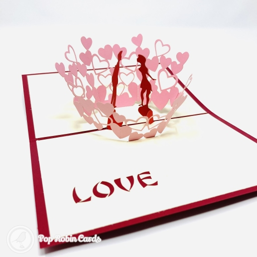 This romantic greetings card opens to reveal a 3D pop-up scene showing in a glade of pink, heart-shaped flowers. The couple move towards each other as the card is flexed. The cover is available in a choice of blue or red, and shows the couple in a stencil design.
