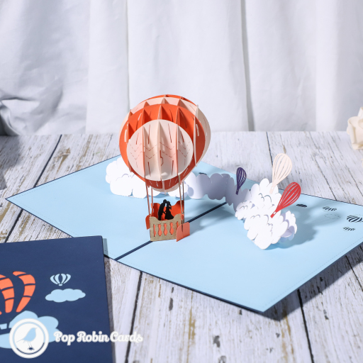 This beautiful romantic card has a 3D pop up design showing a dreamy scene in blue sky and clouds with a couple kissing underneath an orange hot air balloon.