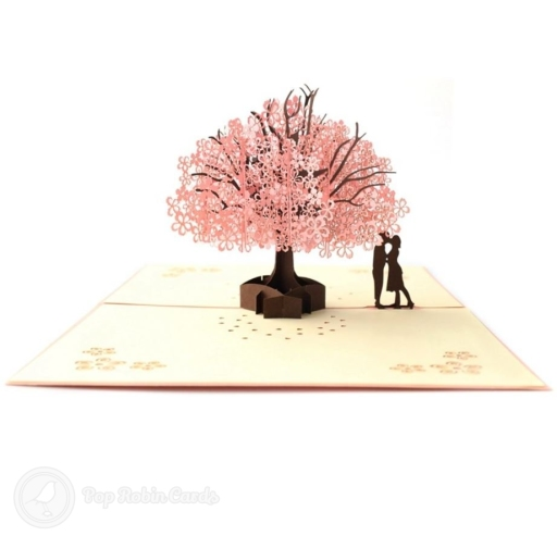 This romantic card opens to reveal a 3D pop-up scene showing a couple below a cherry tree heavy with pink blossom. The cover shows the same scene in 2D collage.