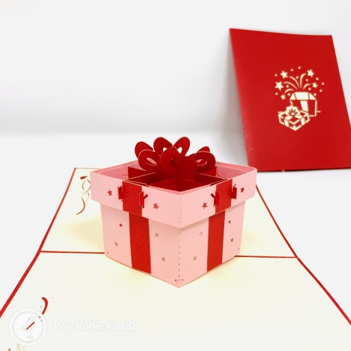 This cute card has a 3D pop up design showing a present wrapped in blue gift-wrap with a red ribbon and bow. The cover has a stencil design showing the gift box being opened and stars bursting out.