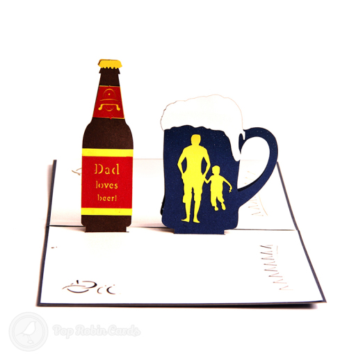 "This card has a 3D pop up design showing a beer bottle with ""Dad Loves Beer"" written on it and an overflowing glass of beer with a father and son stencil design."