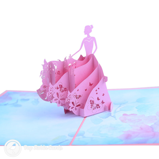 This beautiful card opens to reveal a 3D pop up design showing a girl dancing in a sweeping pink ball gown. The cover has a stencil design showing the same scene.