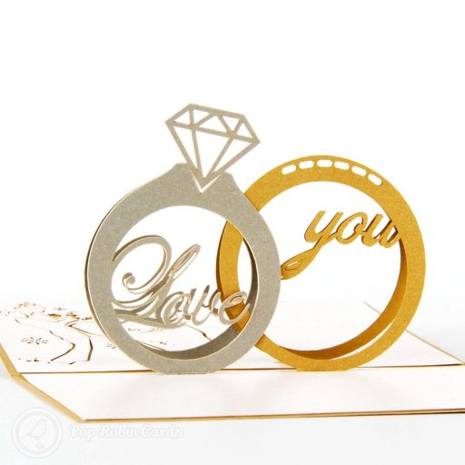 "This card makes an amazing congratulations card for an engagement, marriage or wedding. It opens to reveal a 3D pop-up design showing gold and silver rings, one topped with a diamond, and the words ""love you"" between them."