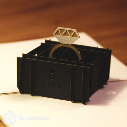 "Ths stylish card is perfect for wedding or engagement congratulations with its 3D pop up design showing a diamond engagement ring in a box. The side of the box has a stencil design showing the word ""Love""."