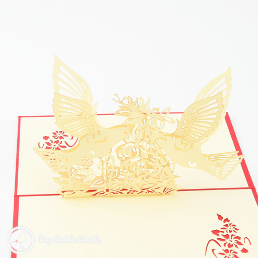 This lovely greetings card opens to reveal a 3D pop up design showing a pair of turtle doves alighting on flowers with their wings extended. The cover has a stencil design showing a turtle dove and flower.