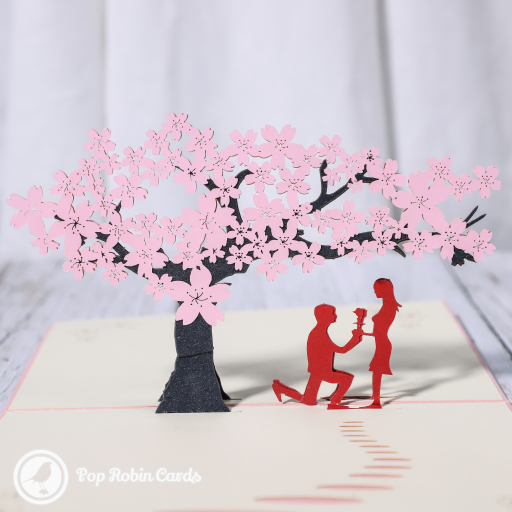 "This beautiful romantic card opens to reveal a 3D pop up design showing a couple giving flowers to each other underneath a tree with pink blossom. The cover has a stencil design with the word ""Sakura"", which is Japanese for ""cherry blossom""."