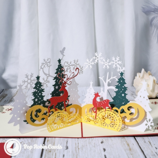 This beautiful Christmas card opens to reveal a stunning 3D pop-up design showing golden reindeer in a winter forest. The cover has a stylish stencil design also showing reindeer in a forest.