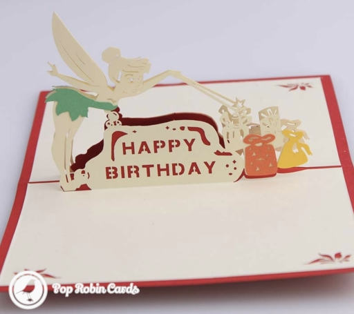 "This cute birthday card has a 3D pop up design showing Tinkerbell the fairy casting a spell on some birthday presents, and a ""Happy Birthday"" message."