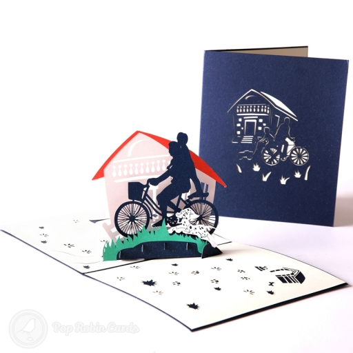 This card has a 3D pop up design showing an idyllic scene with a parent and child riding on a bike together past green grass, with a dog bounding beside them.