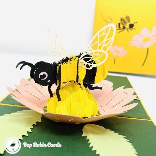 This beautiful greetings card has an amazing 3D pop up design showing a chunky yellow honey bee busily collecting pollen from a pink flower surrounded by green. The cover design shows the bee alighting on pink flowers.