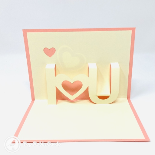 "This simple but effective card has a 3D pop out design showing the message ""I ♥️ U"" in cream and pink colours. The cover has a stylish stencil design showing a heart."