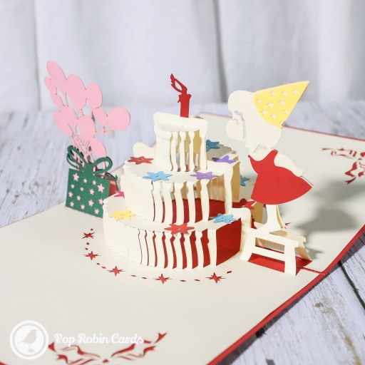 "This cute birthday card has a 3D pop up design shwoing a little girl blowing out candles on a birthday cake, with balloons and presents to one side. The cover has a stencil design with a ""Happy Birthday"" message."