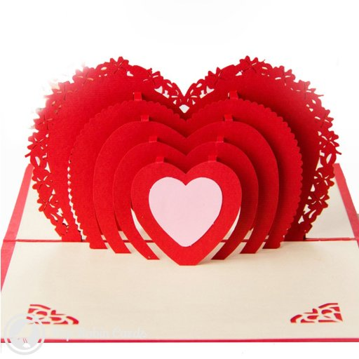 This romantic card opens to reveal a 3D pop-up design showing a deep red love heart in multiple layers. The cover shows a winged heart stencil design.