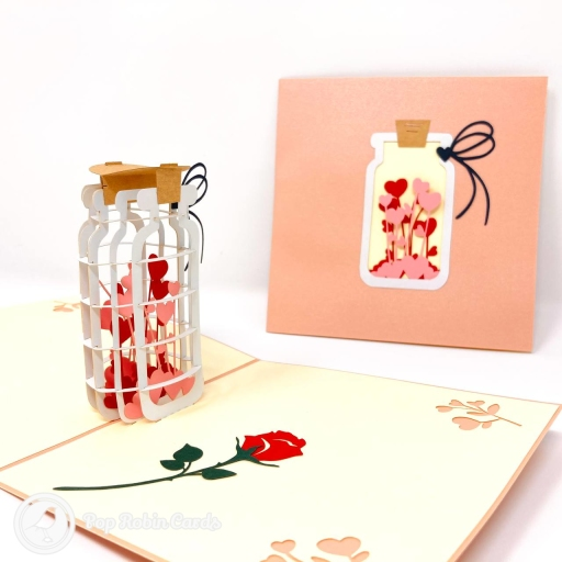 This special and unusual romantic card opens to reveal an amazing 3D pop up design showing pink and red love hearts bottled up and ready to give in a jar. The cover has a layered design showing the same image of love in a jar.