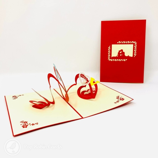 This stylish romantic card opens to reveal a 3D pop up design with a vivid red spiral bearing the letters LOVE, with a heart for the O. The cover has a stencil cut-out design showing a couple sitting together.