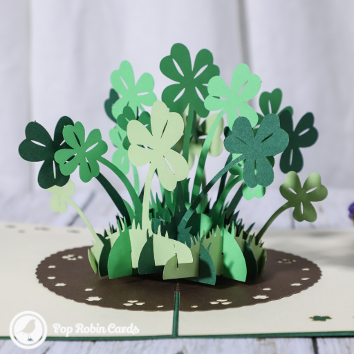 This amazing good luck card opens to reveal a 3D pop up design showing a patch of vivid green four leaf clover plants. The cover has a stylish stencil design showing four leaf clovers.