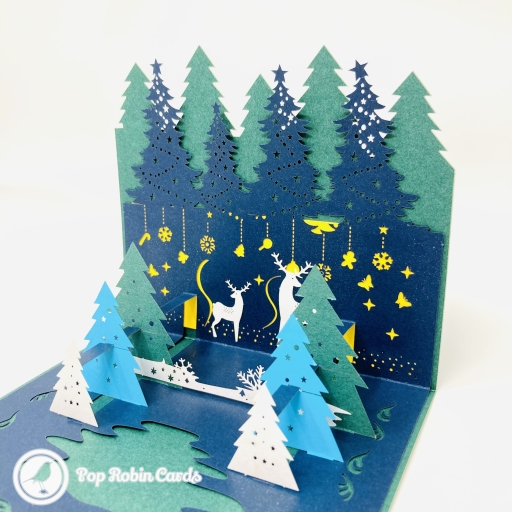 "This beautiful Christmas card opens to reveal a 3D pop up design showing a magical Christmas scene with reindeer in a snowy forest. The cover has a ""Merry Christmas"" message."