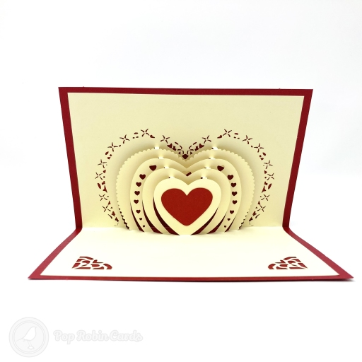 This simple and stylish romantic card has a 3D pop out design showing a red heart backed by many layers of silhouetted hearts. The cover has a stencil design showing a heart flying with wings.