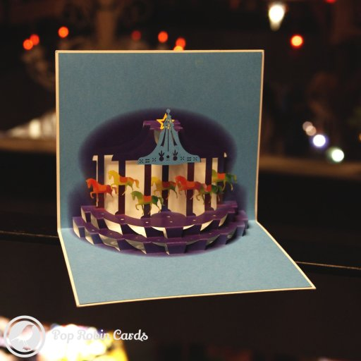 This charming greetings card opens to reveal a beautiful night-time merry-go-round in a 3D pop-up design. The cover has a water-colour painting showing horses on a merry-go-round.