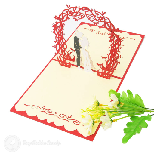 This card is perfect for congratulating a newly wed couple with its 3D pop-up design showing a couple at their wedding under a floral arch. The cover is available in blue or red colours and has a stencil design.