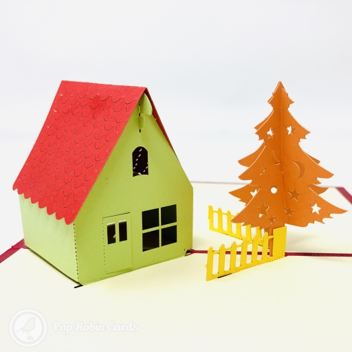 This simple but tasteful Christmas card has a stylish 3D pop-up design showing a cosy Christmas lodge in a snowy landscape with a Christmas tree.