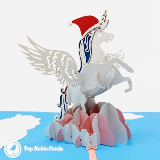 This fabulous Christmas card has a 3D pop up design showing a winged unicorn wearing a red Christmas hat flying through the clouds. The cover has a stencil design also showing the unicorn.
