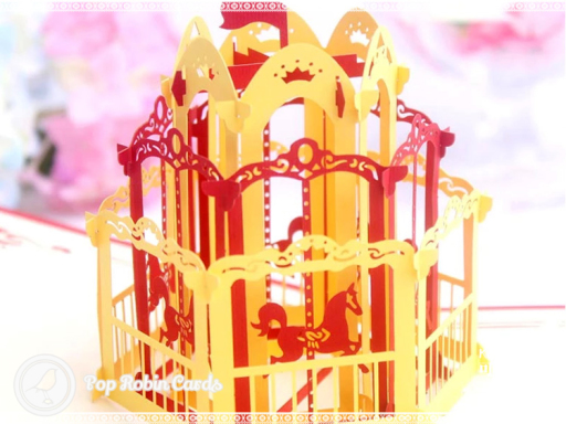 This charming greetings card has a 3D pop up design showing a brightly coloured merry-go-round carousel. The cover has a stencil design showing the horses on the carousel.
