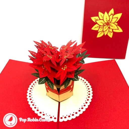This floral and festive card has a 3D pop up design showing vivid red poinsettia flowers with green leaves in a basket. Its perfect for many occasions, including Christmas when poinsettia flowers are traditionally used in festive displays.